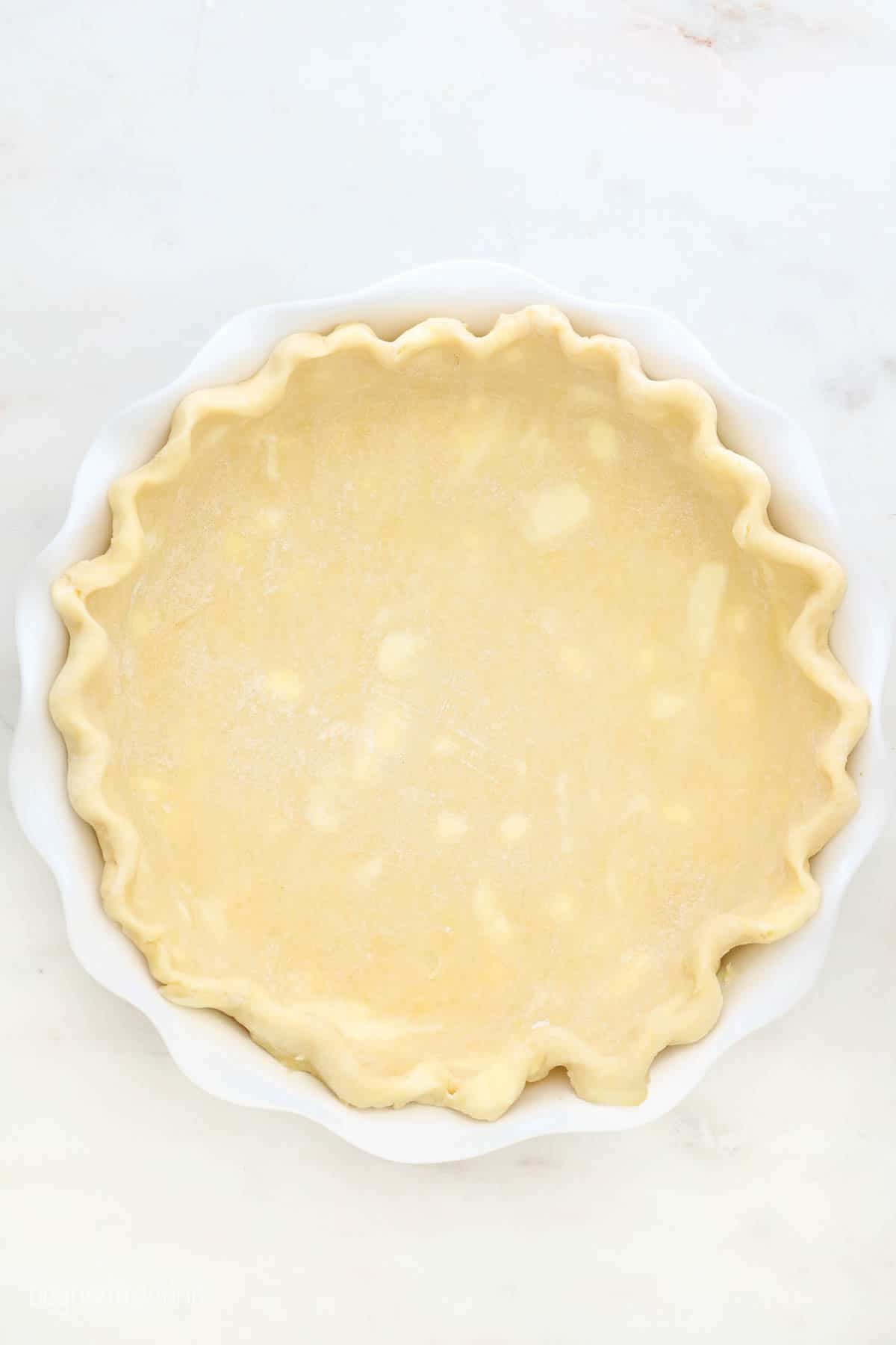 An unbaked pie crust with crimped edges and chunks of cold butter in it