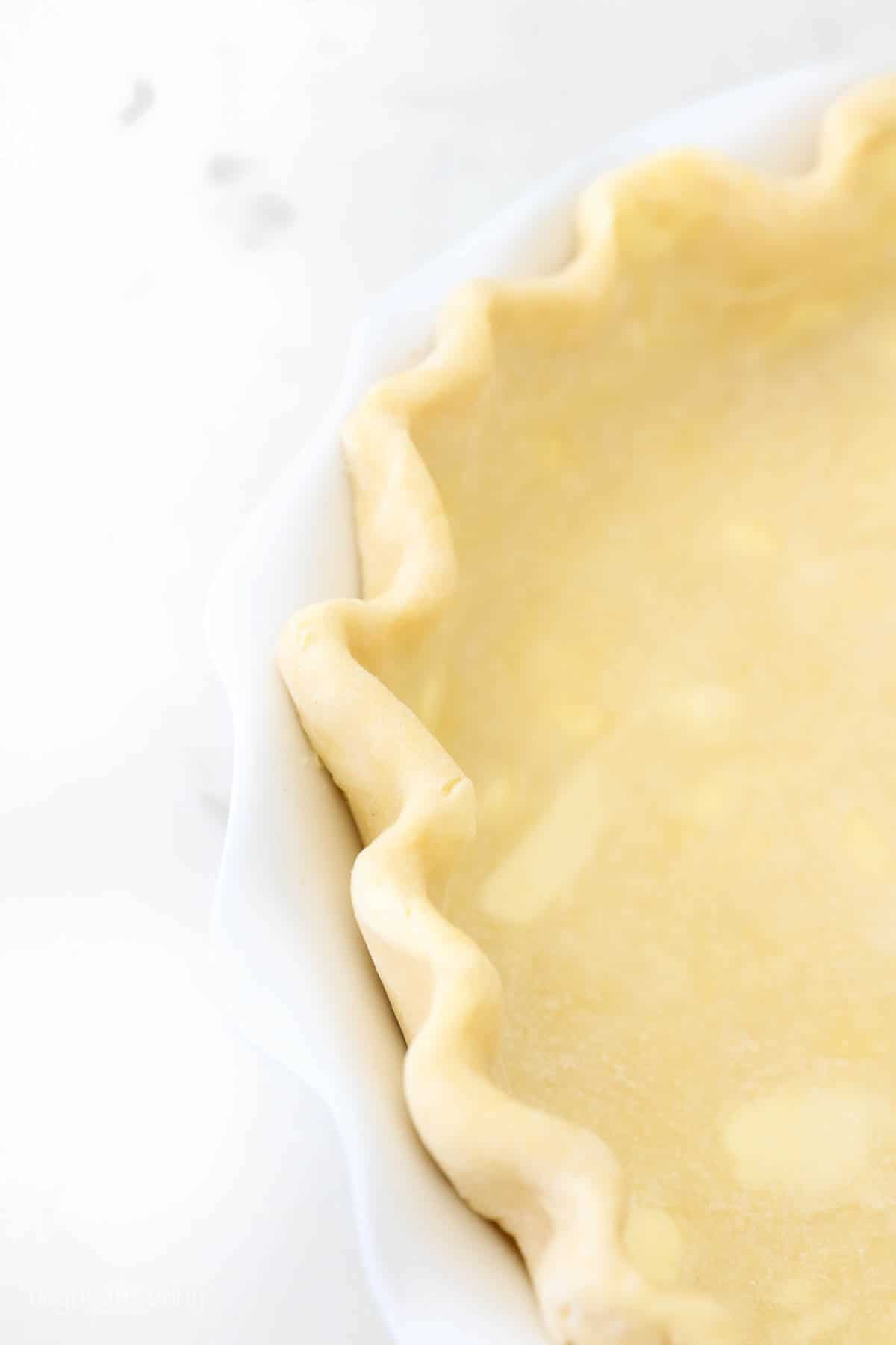 A close-up shot of the crimped edges of a homemade butter pie crust
