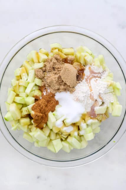a glass mixing bowl with chopped apples, cinnamon sugar, brown sugar and flour