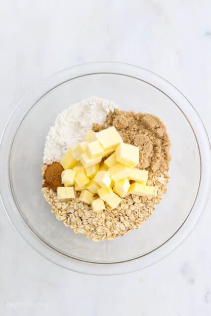a glass mixing bowl with butter, oats, brown sugar, flour and cinnamon