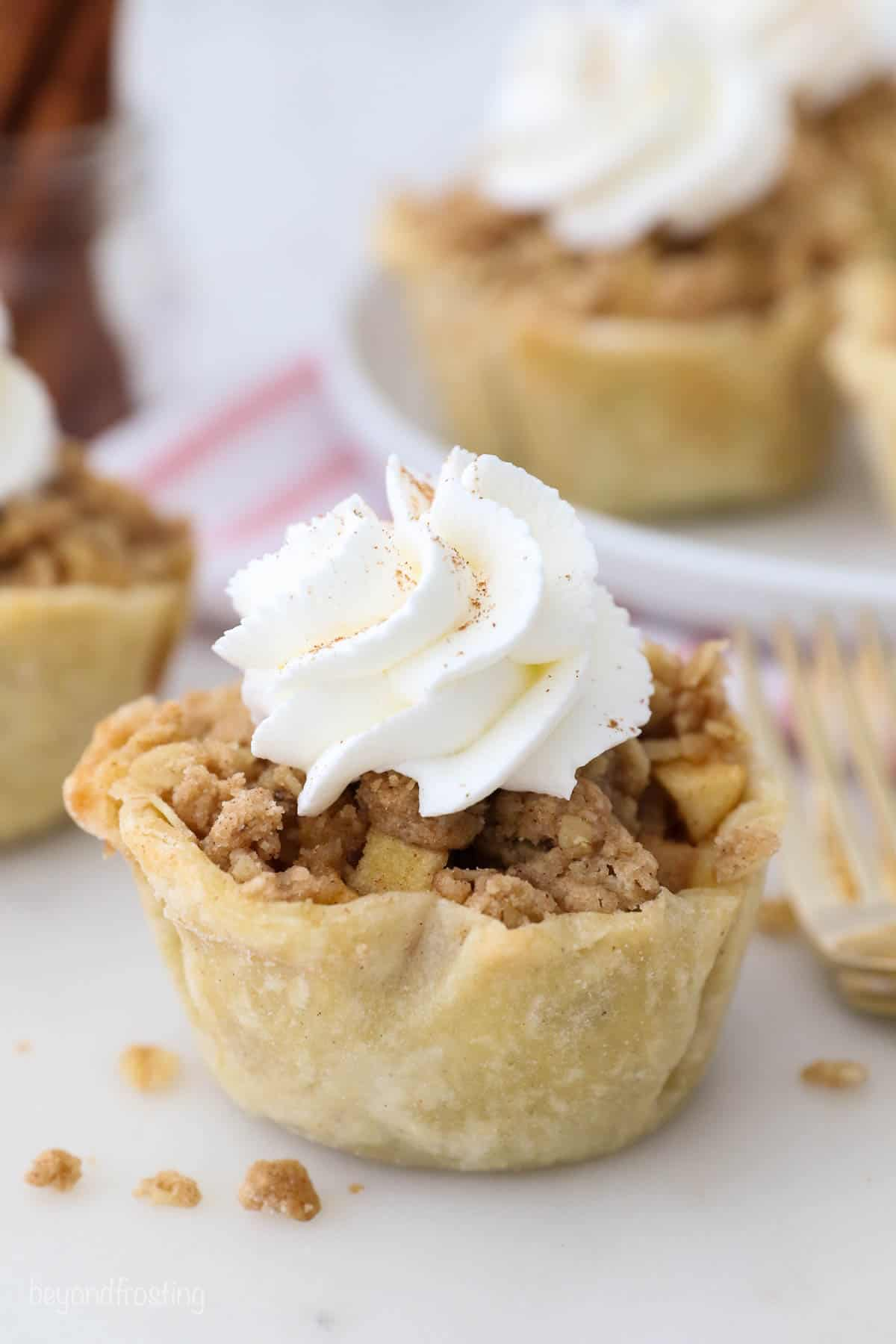 A close up of a small apple pie with whipped cream topping