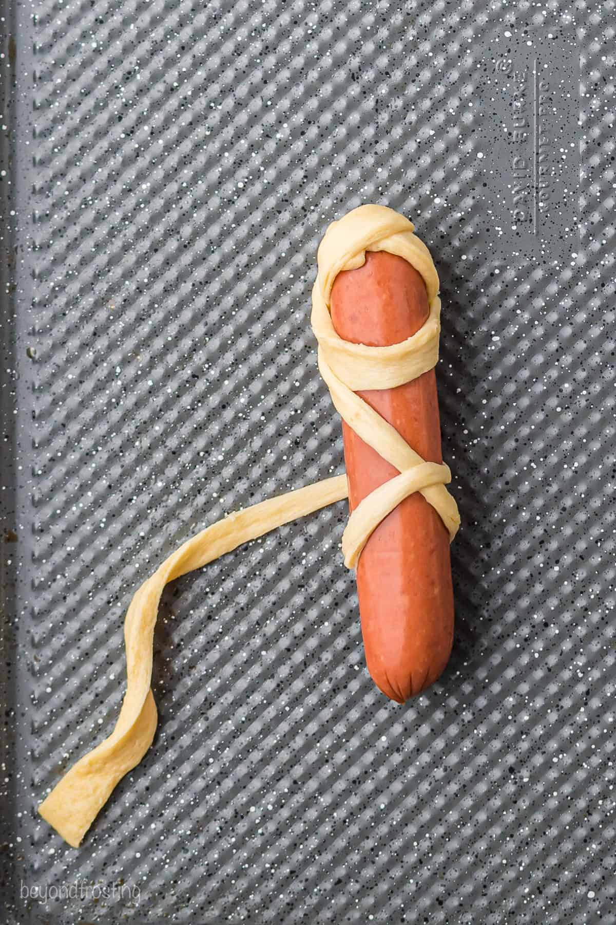 A raw hot dog being wrapped with a strip of crescent dough