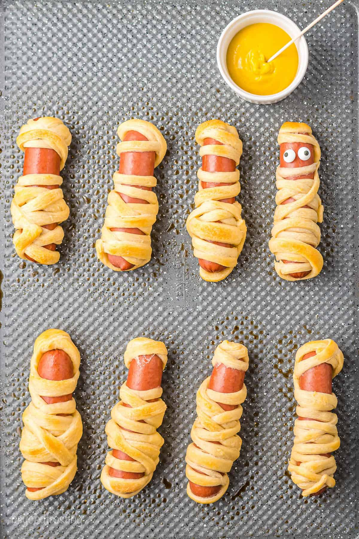 Eight mummy hot dogs on a lined baking sheet with candy eyes on one of them