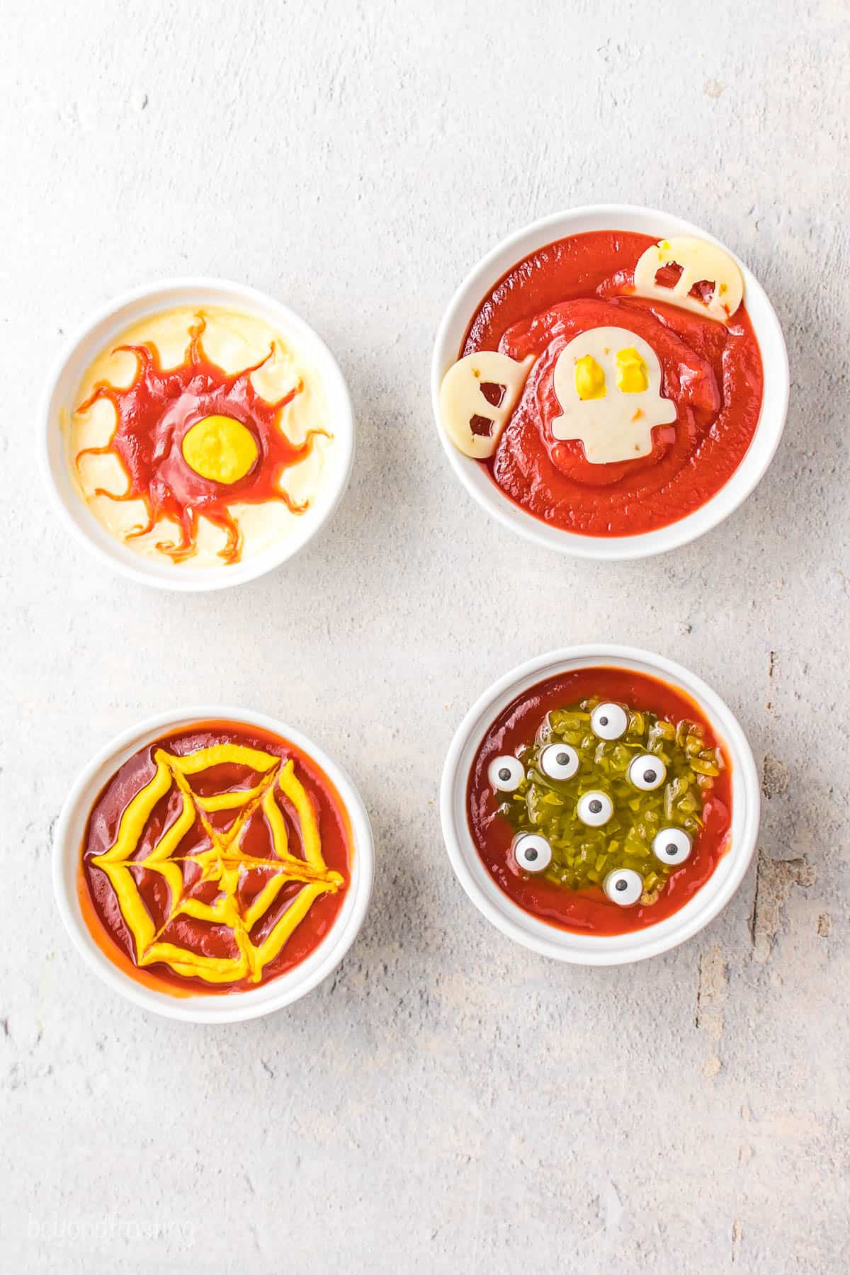 A bowl of spiderweb dip, a bowl of bloodshot eye dip, a bowl of ghost dip and a bowl of monster puddle dip on a countertop