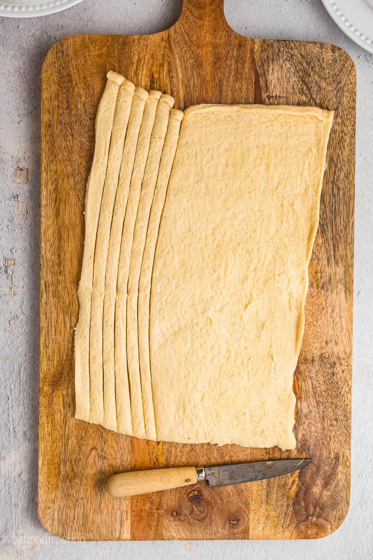 A Pillsbury crescent dough sheet with 6 thin strips cut off of it