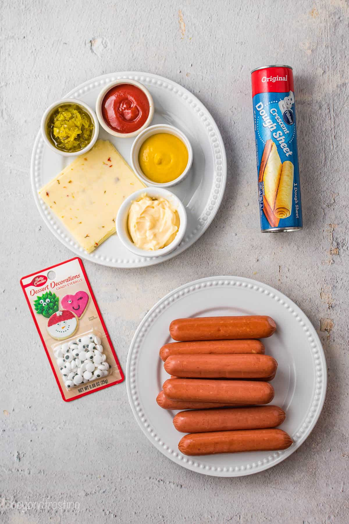 A package of candy eyes, a plate of hot dogs and the rest of the mummy dog and spooky dip ingredients on a gray surface
