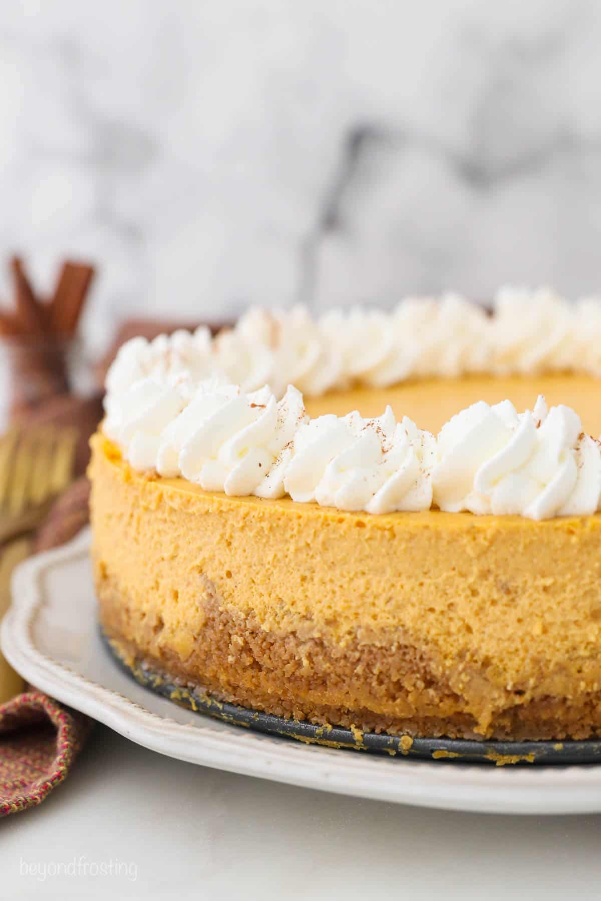 A fall-spiced cheesecake on a serving platter with homemade whipped cream along the top edge