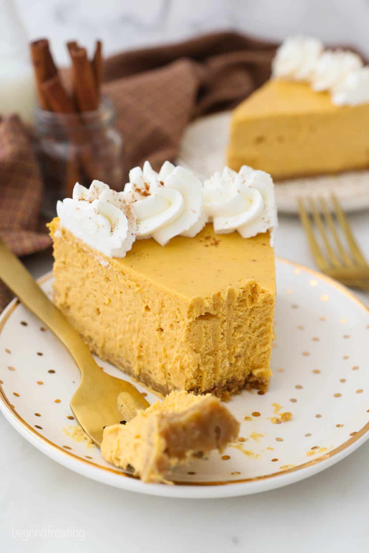 A piece of pumpkin cheesecake on a plate with one bite on a golden fork