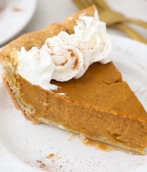 a slice of pumpkin pie topped with whipped cream on a white plate