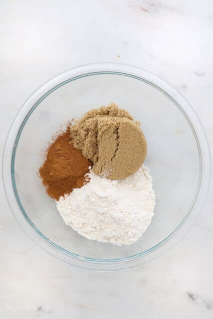 a glass mixing bowl with brown sugar, cinnamon and flour