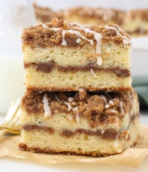 Twice slices of layered coffee cake on a piece of brown parchment paper and gold forks