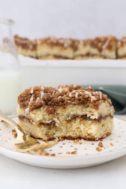 a slice of coffee cake with a few bites taken out on a gold polk dot plate with a gold fork,