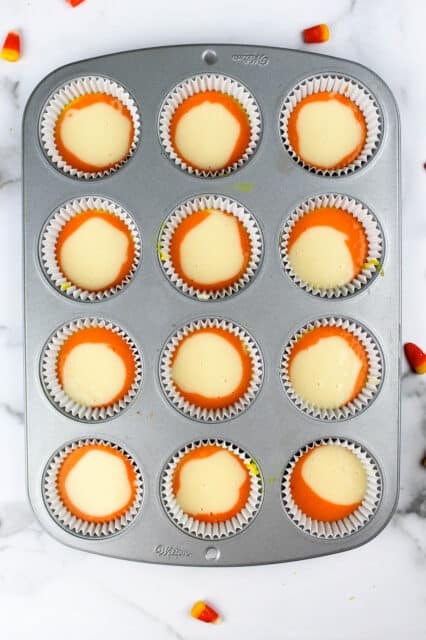 a cupcake pan filled with orange and white batter