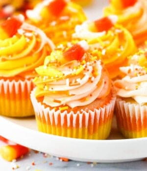 A close up of a candy corn cupcake on a white rimmed plate