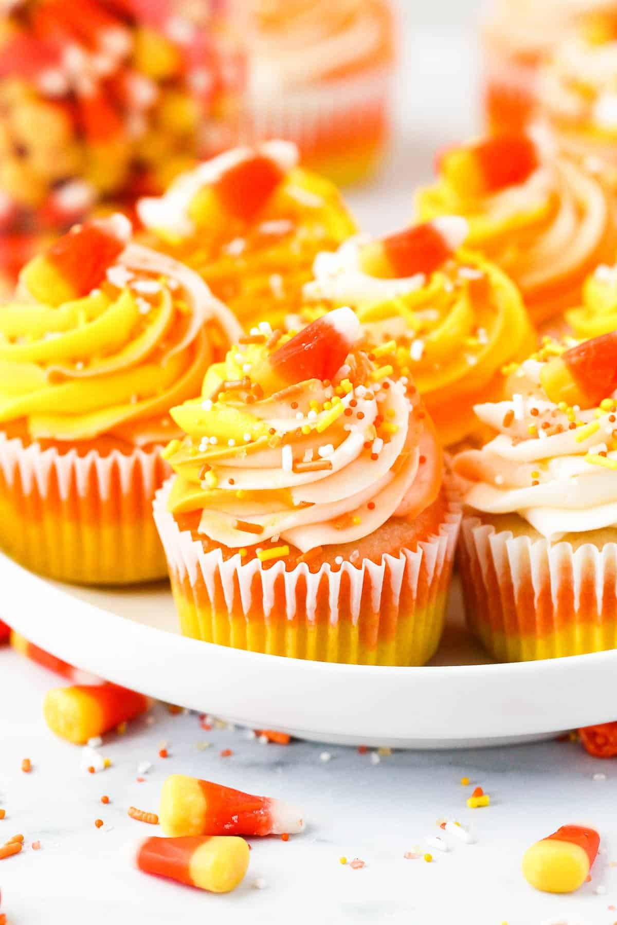A white plate with cupcakes decorated to look like candy corn