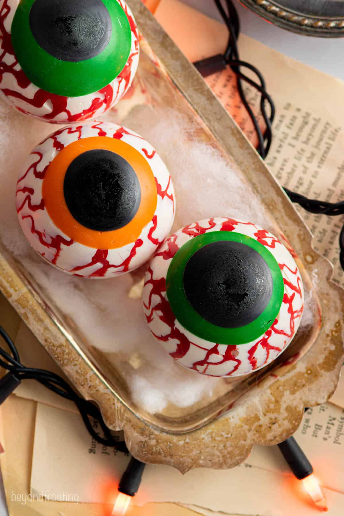 three halloween hot chocolate bombs decorated to look like eyeballs on a vintage metal tray