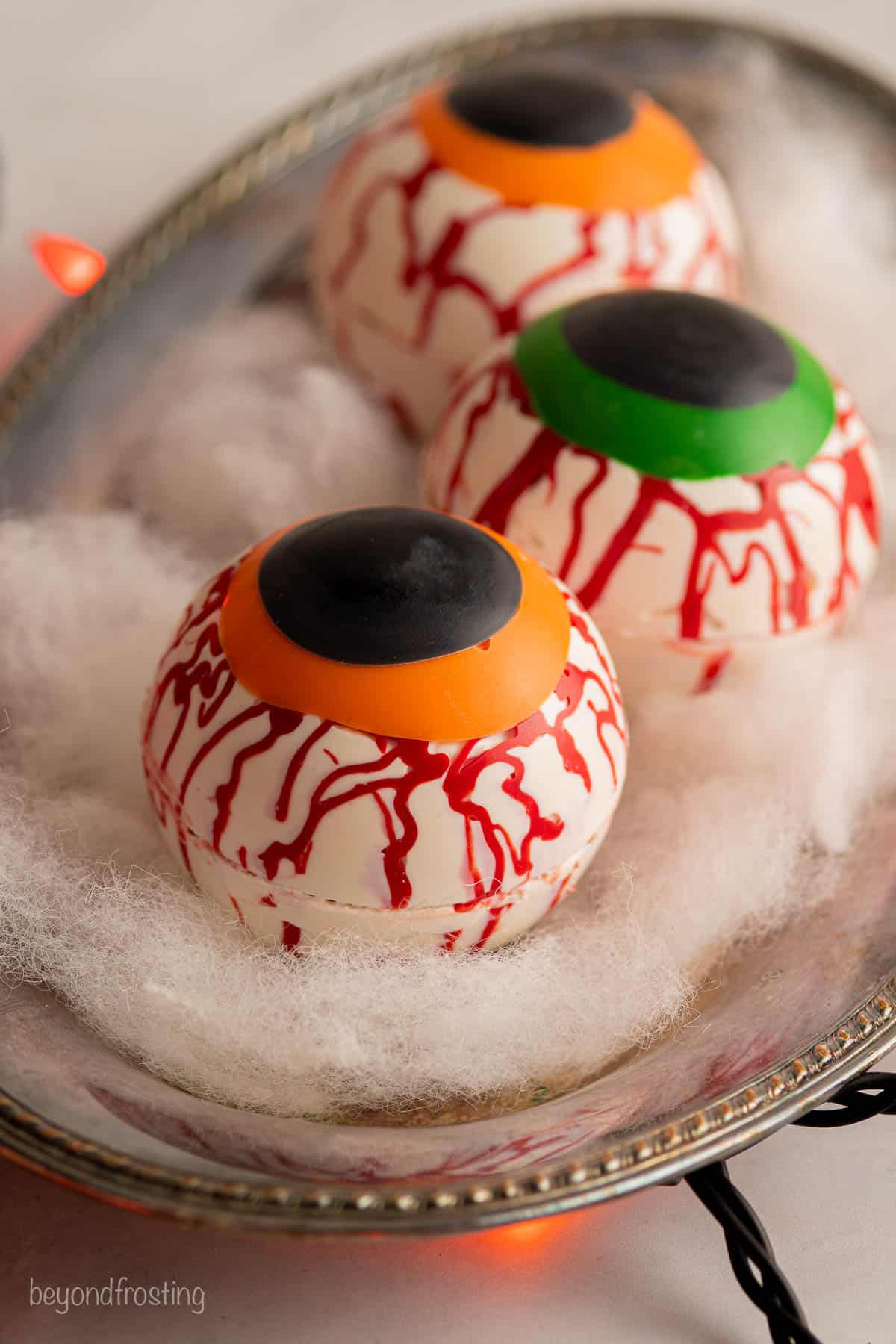 three halloween hot chocolate bombs decorated to look like eyeballs