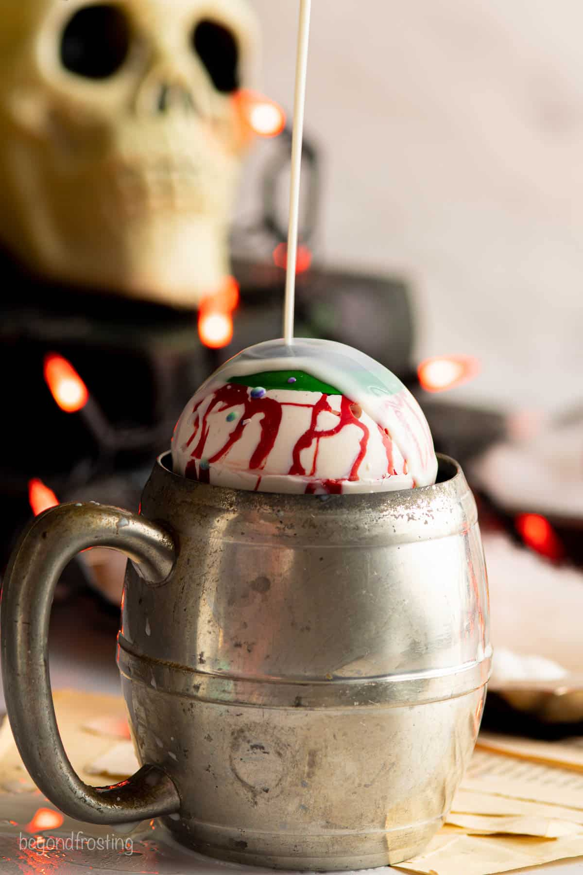 Milk being poured over a hot chocolate bomb in a vintage metal mug