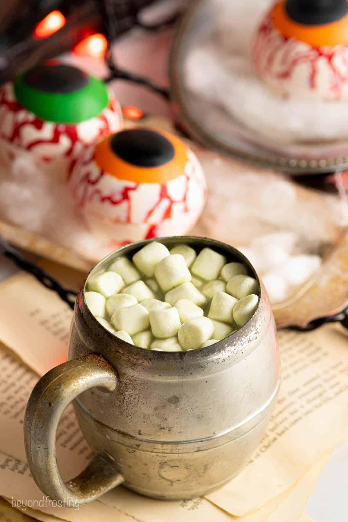 a vintage metal mug with hot chocolate and mini marshmallows