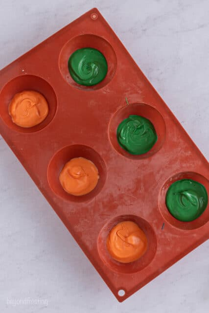 a red silicone mold with 6 cavities filled with green and orange candy melts
