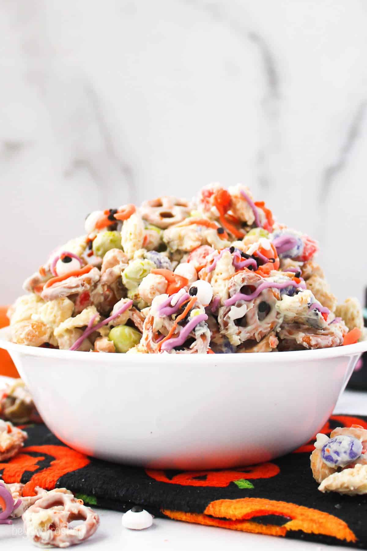 a white bowl sitting on a pumpkin towel. The bowl is filled with with a halloween snack mix