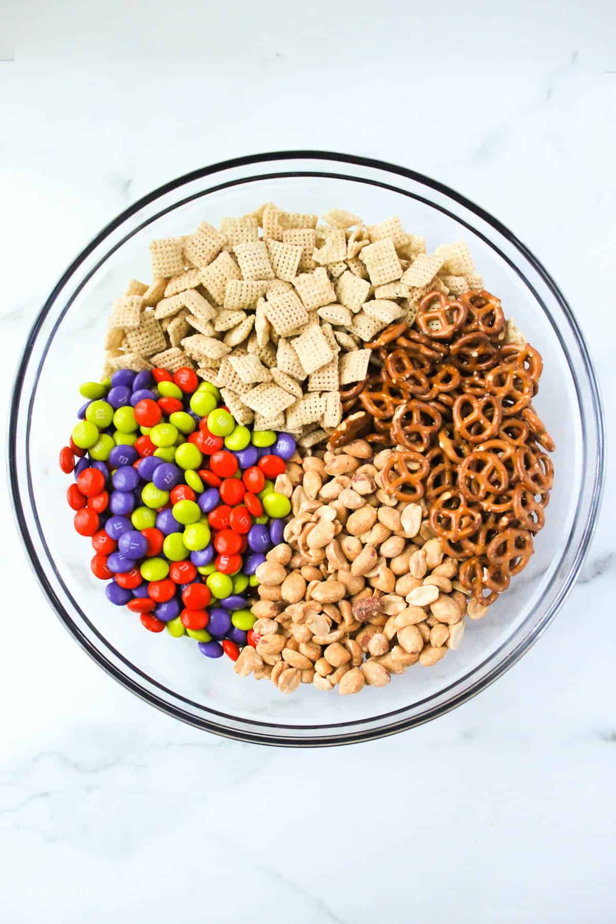 a glass mixing bowl with chex ceral, cereal, peanuts and M&Ms