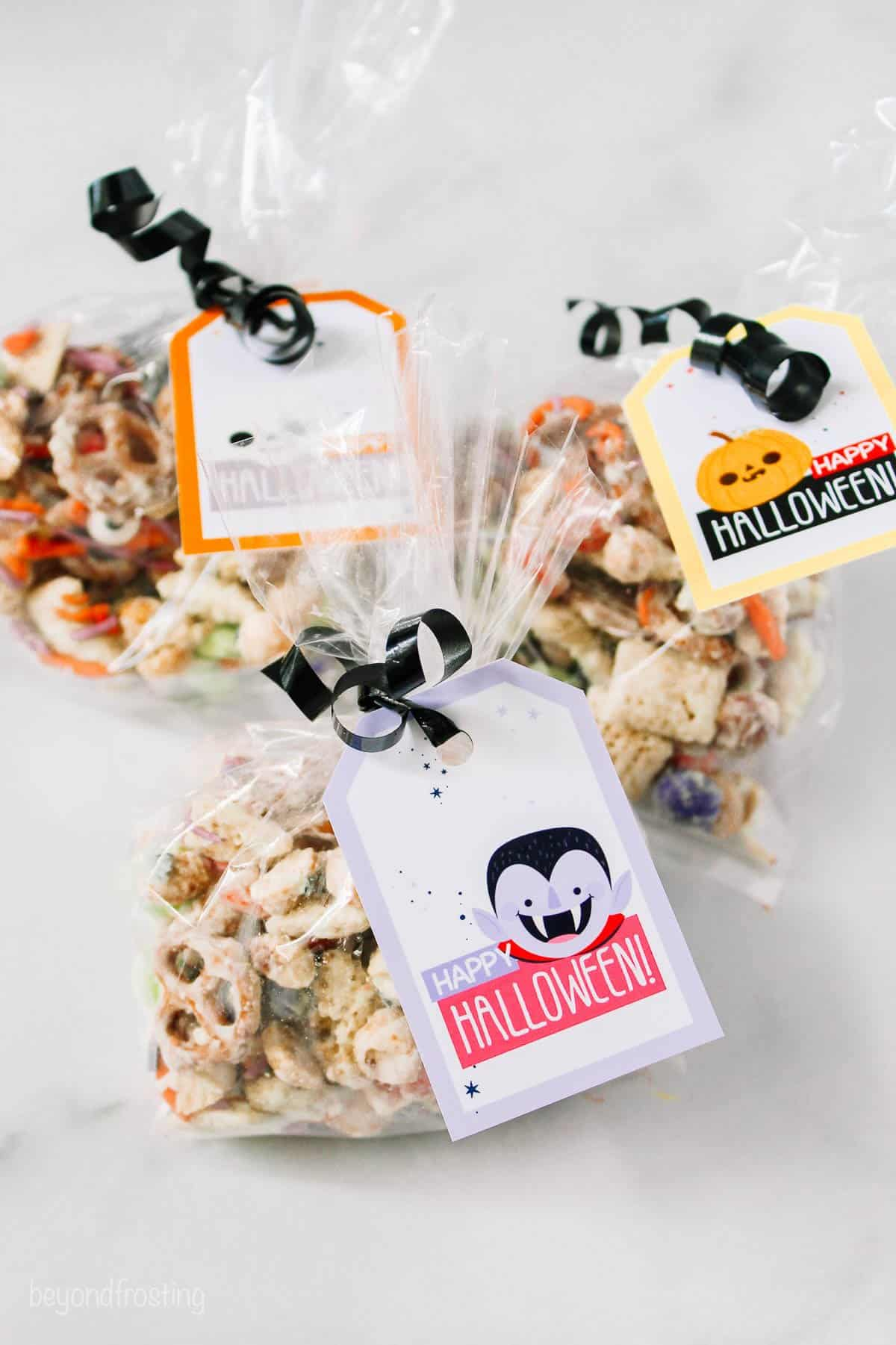 three plastic bags with halloween tags and black ribbon