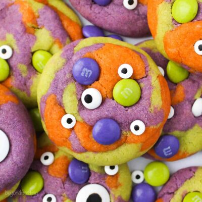 close up shot of halloween monster cookie- tye dye orange, purple and green with M&Ms and candy eyes