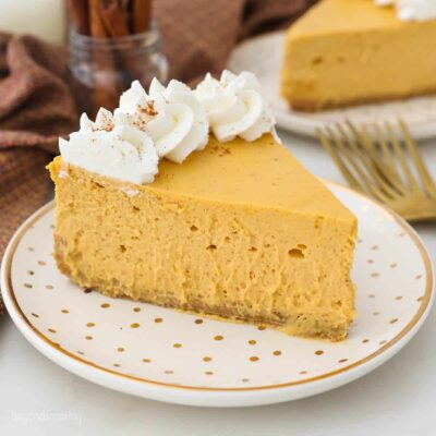 A gold polka dot plate with a slice of pumpkin cheesecake garnished with whipped cream
