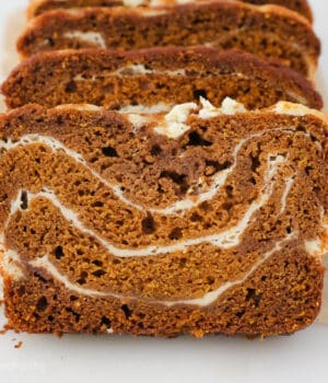 A close up shot of sliced pumpkin bread with swirls of cream cheese filling