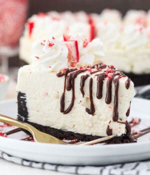A sliced peppermint cheesecake on a white plate with dripping chocolate drizzle